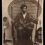 Huey Newton seated in wicker chair holding weapons poster SM