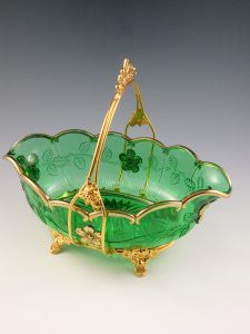 "Paneled dogwood pattern on an oval basket in green and gold. Riverside Glass, 1880-1900. 12"" longest side, $700-$800."