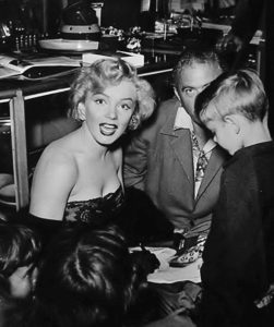 Marilyn Monroe signing autographs for a young fan while out on the town.