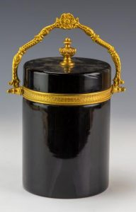 Vintage gold gilt dore bronze mounted black opaline glass casket. Features gilt mount with a cylindrical form and lid and articulated handle at Hill Auction Gallery, estimated to sell for up to $1,000