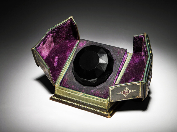 """A 1926 Baccarat for Isabey """"Tresor Cache"""" presentation of Lys black crystal perfume bottle and stopper as a faceted jewel with cord seal, label and tooled leather box sold for $56,250 at an auction held July 11 by Perfume Bottles Auction in New York City"""
