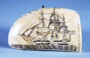 """Authentic American scrimshaw can bring big bucks at auction. In 2017, Osana's Auction sold a sperm whale tooth with crisp, clear carvings of the Pacific of Nantucket, signed in cursive """"Made.By.Edward.Burdett"""" on the base. Bringing $252,000, this exquisite piece showed two scenes- the ship under full sail on the starboard side, and on the reverse, the port side under reduced sail with a whale alongside, engaged in the """"cutting in"""" process. photo: Osana Auctions, Nantucket"""
