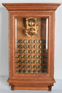 A Gamewell Excelsior fire alarm transmitter with 50 code wheels, in a refinished oak case with beveled-glass front door, sold for $7,800 at a sale of the Brian Maiher collection of railroadiana, petroliana, and antique fire alarms held August 29 by Milestone Auctions in Willoughby, OH