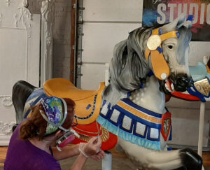 Here Restorations Manager Lisa Ronalter applies pinstriping to a horse bound for the carousel at Sonny's Place in Somers, CT, an antique machine built in 1925 by the Philadelphia Toboggan Company.