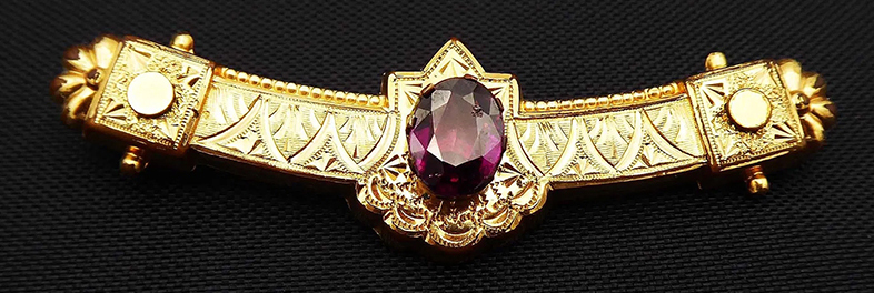 Victorian brooch featuring oval January birthstone (garnet) on rolled gold bar  pin c. 1880s-1910s selling for $60 online