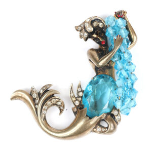 Eisenberg Originals iconic sterling vermeil mermaid brooch holding strands of aquamarine crystals, with faceted open-backed aquamarine crystal torso and red enamel lips, mid-1940s. Advertised in Vogue magazine, circa 1946. Sold for $4,500