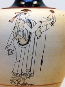 A ca. 490 BC design on a Greek attic oinochoe (wine jug) of a woman spinning thread.