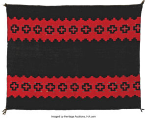 A circa 1870 classic Navajo Woman's Manta, sold at Heritage Auctions for $31,070. It measures 41 by 53 1/2 inches and features two bands of Spider Woman crosses set against a red background, a brown center, and indigo blue end zones. photo: Heritage Auctions, HA.com.