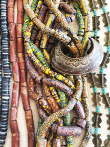 """West African peoples have adorned themselves with Venetian millefiori beads, intermixed with locally-made jewelry (left to right): blue-and-white """"sand beads"""" made from powdered glass Vicks and Milk of Magnesia jars (Krobo and southern Ghana groups); reddish-brown bauxite, or aluminum ore, beads (Ghana); cast bronze bracelet (Baule); and cast bronze beads (Ashante)."""