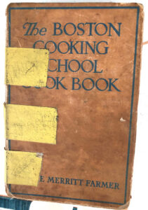 A well-loved and taped-together example of The Boston Cooking School Cook Book by Fannie Merritt Farmer