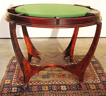 An impressive George Hunzinger Mahogany flip top yacht game table, c.1890s. This superb round gaming table has a mahogany veneered top which reverses to reveal a gaming table with a green baize surface, surrounded by wells for gaming pieces. The tabletop swivels on rods through two of the four leg top terminals. The other two leg-top terminals have a metal spring-loaded catch mechanism that holds the tabletop in place and allows it to swivel when the catch is depressed.