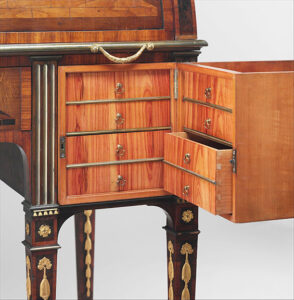 Rolltop desk, ca. 1776-79, was a technical marvel created by David Roentgen of Germany. Secret elements include the resulting surprises from turning the central key to the right (see detail of keyhole, shown) when the compartment to the right of the kneehole slides forward. A button underneath can be pressed to release its front half. This swings aside to reveal two drawer panels, each with four Birmingham Chippendale-style pulls. photo: metmuseum.org