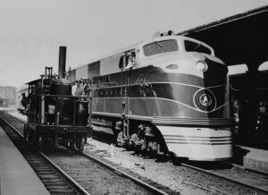 A vintage 1937 original photograph depicting Baltimore & Ohio Railroad introducing its newest with its oldest. The famous Tom Thumb is posed with a shiny EA built by Electro-Motive Corporation of La Grange, Illinois.