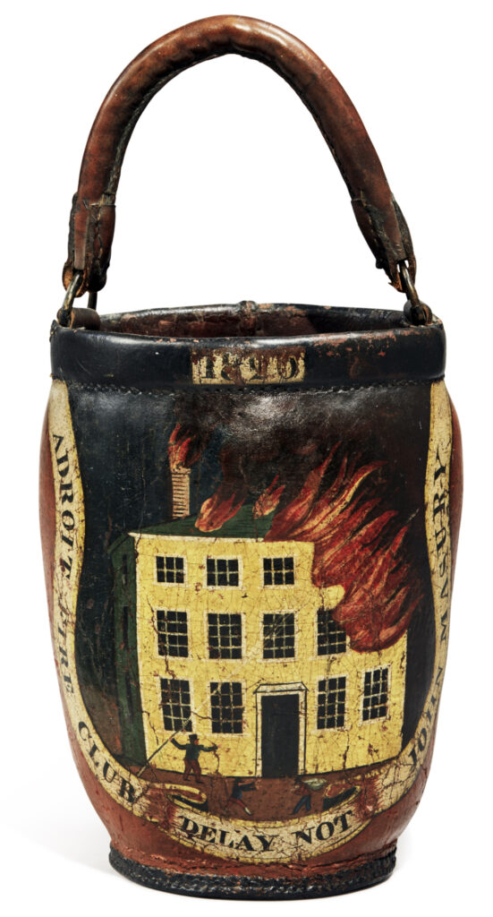 """1. Club fire buckets were decorated with their chosen logo, and few examples are as impressive as this Adroit Fire Club example from Salem, MA, ca. 1820. Emblazoned with the club's name, the owner's name, and the motto """"Delay Not,"""" this striking example depicts men fighting to save a Federal-style house from burning. According to Sotheby's, which sold the bucket for $40,000 in 2020, other examples from the Adroit Fire Club carry on the theme of the burning house surviving. photo: Sotheby's, Triumphant Grace: Important Americana from the Collection of Barbara and Arun Singh, 2020"""
