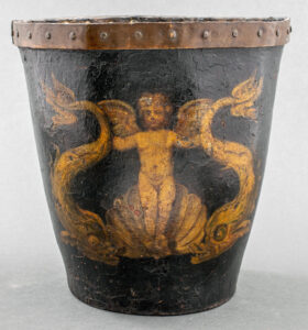5. An example of an English paint decorated leather fire bucket with a metal band, 18th/19th century, showing nautical motifs of a winged cherub rising from a wave with a dolphin in each hand. This example is part of a New York City estate auction with an estimate of $400-$600, indicative of the current market for a good example with a whimsical theme.